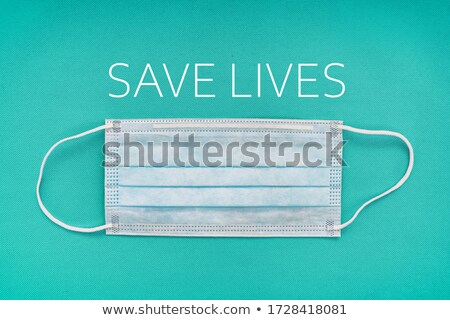 COVID-19 Coronavirus mask sign with text SAVE LIVES media message for social distancing precaution.  Stock photo © Maridav