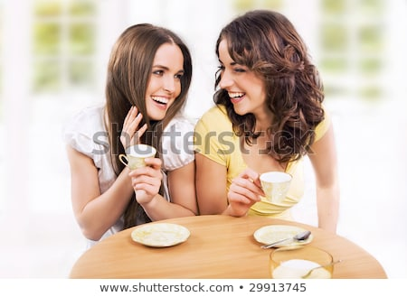 two beautiful women drinking coffee and chatting at mall cafe stock photo © hasloo