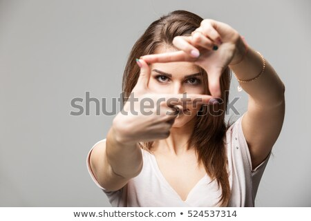 Attractive young woman making a picture frame with her fingers  Stock photo © williv