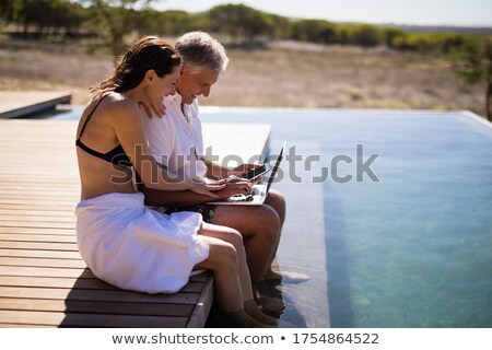 Couple using a laptop by the poolside Stock photo © photography33
