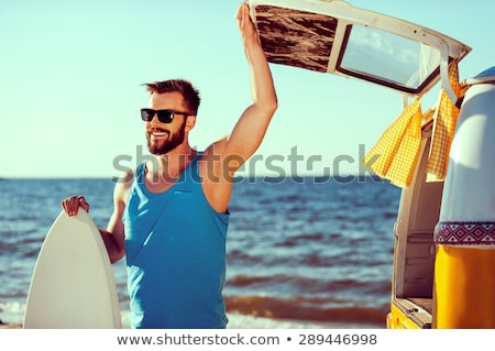 Young man at the beach with surfboard stock photo © photography33