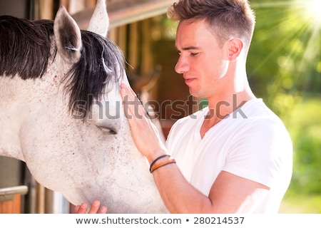 Foto stock: Blond Woman Petting Horse