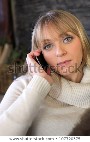 Blond woman in winter jumper sat on sofa Stock photo © photography33