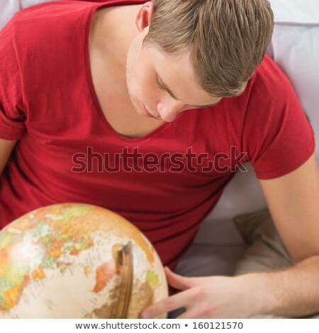portrait of a handsome young man sitting at home with globe and stock photo © hasloo