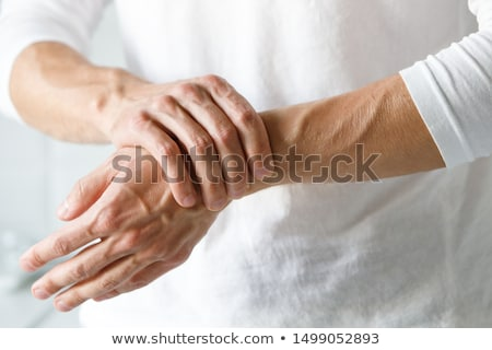 man holding hand with wrist pain stock photo © deandrobot