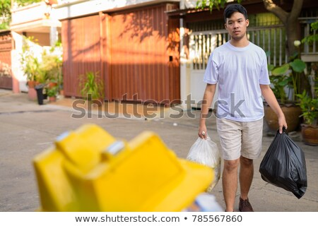 portrait of man taking out garbage in bags stock photo © highwaystarz