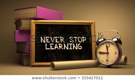Never Stop Learning Handwritten by white Chalk on a Blackboard. Stock photo © tashatuvango