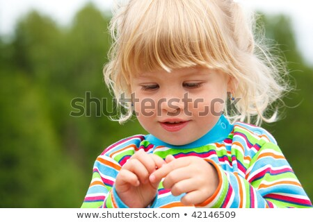 Portrait of little girl in stripe clothe with earrings in park.  Stock photo © Paha_L