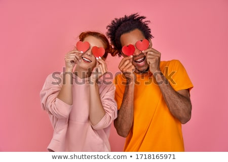 smiling woman covering eye with orange stock photo © deandrobot