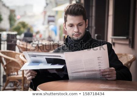 Uomo magazine seduta outdoor cafe attrattivo Foto d'archivio © deandrobot