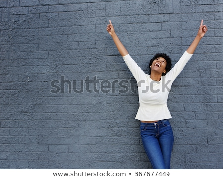 Portrait of a happy smiling woman standing with hands raised Stock photo © deandrobot
