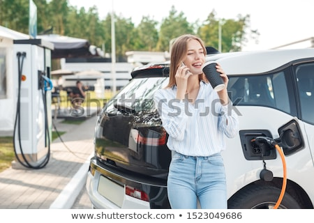 Young woman drinking by electric car Stock photo © IS2