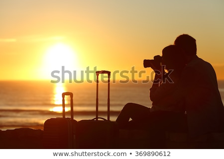 Girls photographing sunset on beach Stock photo © bezikus