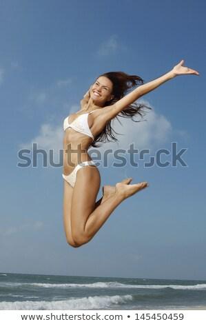 Eccitato donna bikini jumping spiaggia mani Foto d'archivio © wavebreak_media