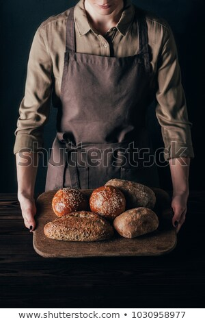 partial view of woman holding loafs of bread on wooden cutting board isolated on black stock photo © lightfieldstudios