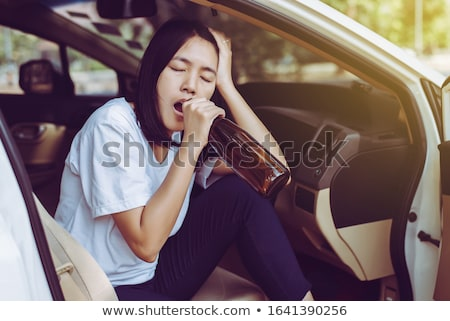 woman holding beer bottle while driving car stock photo © andreypopov