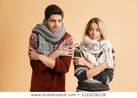 Portrait of a frozen young couple dressed in sweaters Stock photo © deandrobot