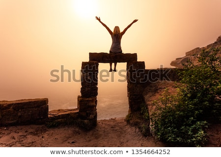 Female sits on top of doorway to the unknown realm Stock photo © lovleah