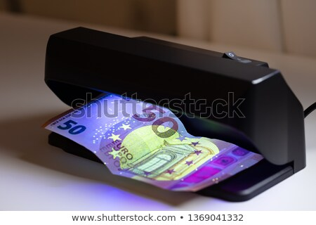 Banknote And Banknote Detector Machine On Desk Stock photo © AndreyPopov