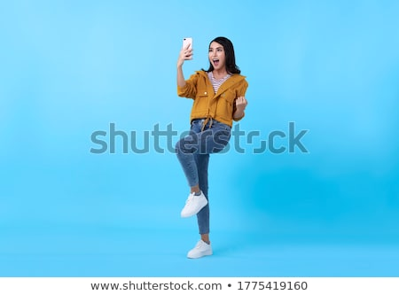 Asian beautiful woman isolated over blue background using mobile phone. Stock photo © deandrobot