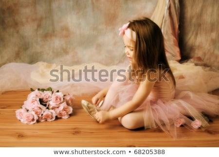adorable little girl dressed as a ballerina in a tutu tying her ballet slippers stock photo © elenabatkova