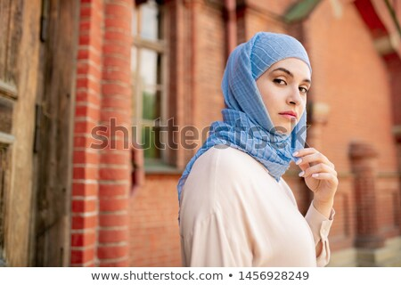 Young serious Arabian female in blue hijab chilling out in ancient city Stock photo © pressmaster