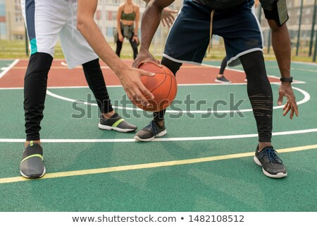 Young intercultural sportsmen in activewear playing basketball on outdoor court Stock photo © pressmaster