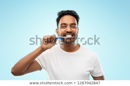 indian man with toothbrush over blue background Stock photo © dolgachov