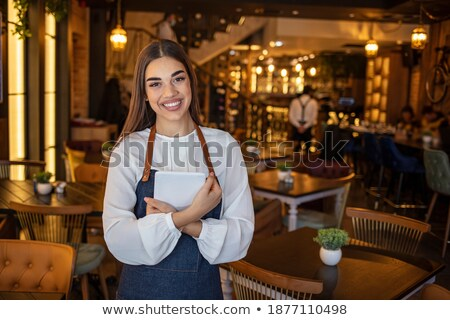 businesswoman looking at camera while using digital tablet in restaurant stock photo © wavebreak_media