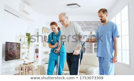 Seniors in rehabilitation learning how to walk with crutches Stock photo © Kzenon