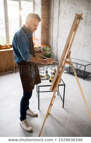 Casual homem avental em pé cavalete pintura Foto stock © pressmaster