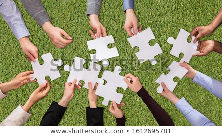 People Hands Joining The White Jigsaw Puzzles On Turf Stock photo © AndreyPopov