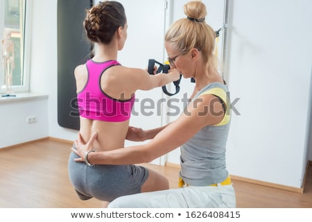 Woman using sling trainer during physical therapy Stock photo © Kzenon