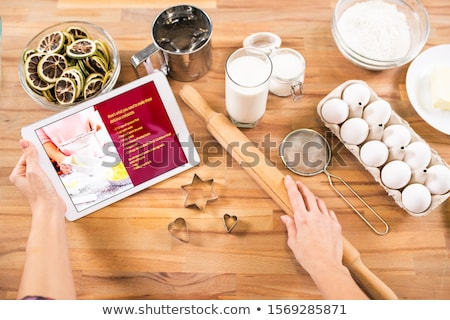 housewife holding tablet and rolling-pin while going to cook pastry at home Stock photo © pressmaster