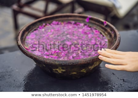 Balinese basin with flower petals on the background of the pool Stock photo © galitskaya