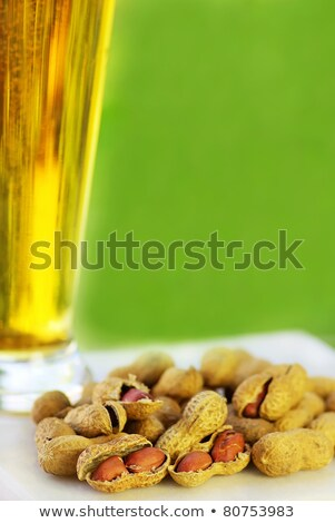 glass of cold beer with peanuts ongreen background  Stock photo © inaquim