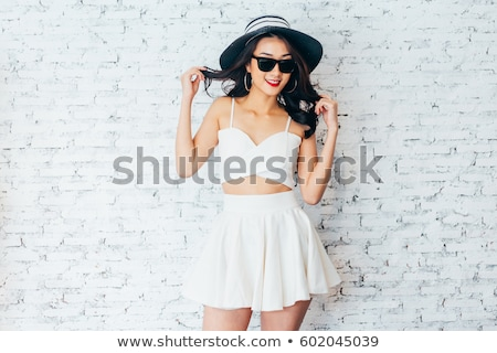 woman in black dress over brick wall stock photo © dolgachov