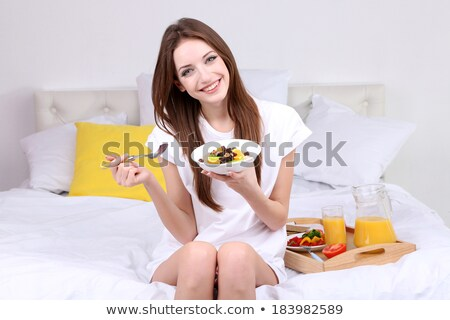 Portrait of young woman holding cookie and fruit bowl stock photo © wavebreak_media