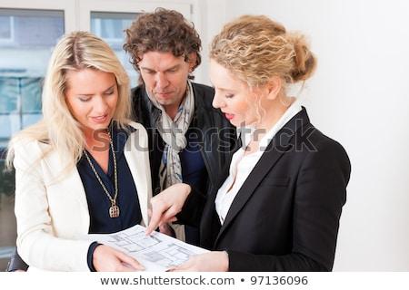 Young realtor explaining ground plan to couple Stock photo © Kzenon