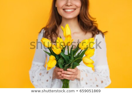 cropped image of a woman holding flowers stock photo © deandrobot