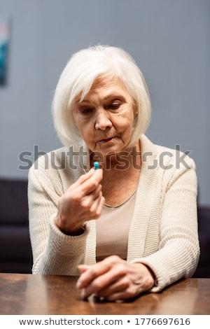 Lehangolt nő tart tabletták izolált fehér Stock fotó © deandrobot