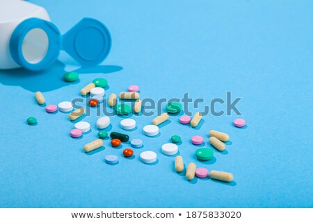 Scattered from medical bottle red and blue pills Stock photo © ironstealth