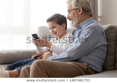cheerful little boy in glasses sitting and using smartphone stock photo © deandrobot