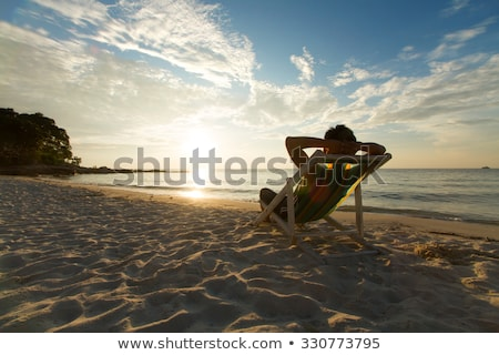 Stock photo:   deckchairs and man on beach at sunset