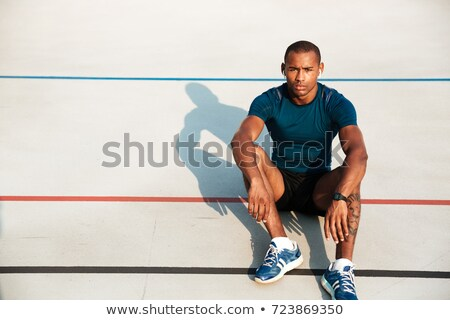 Handsome young sports man at the stadium listening music Stock photo © deandrobot