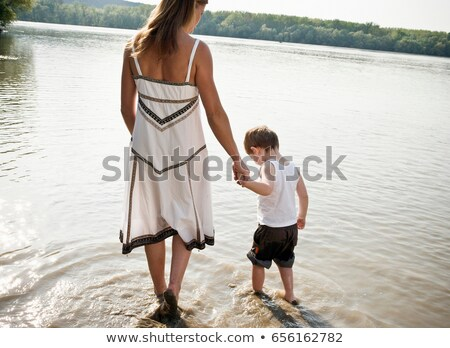 Mother guiding child in river Stock photo © IS2