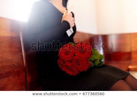 close up of woman with roses at funeral in church Stock photo © dolgachov