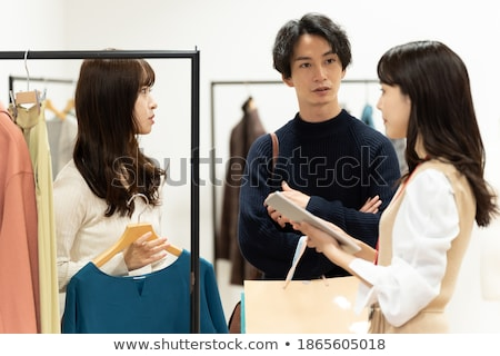 attractive young couple standing at the clothing store stock photo © deandrobot