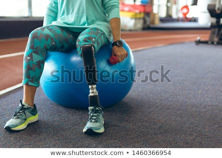 Disabled sports woman sitting in gym. Stock photo © deandrobot