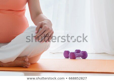 pregnant woman meditating and practicing yoga in her bedroom stock photo © boggy